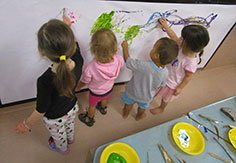 Kids painting a large wall mural at Broome Day Care